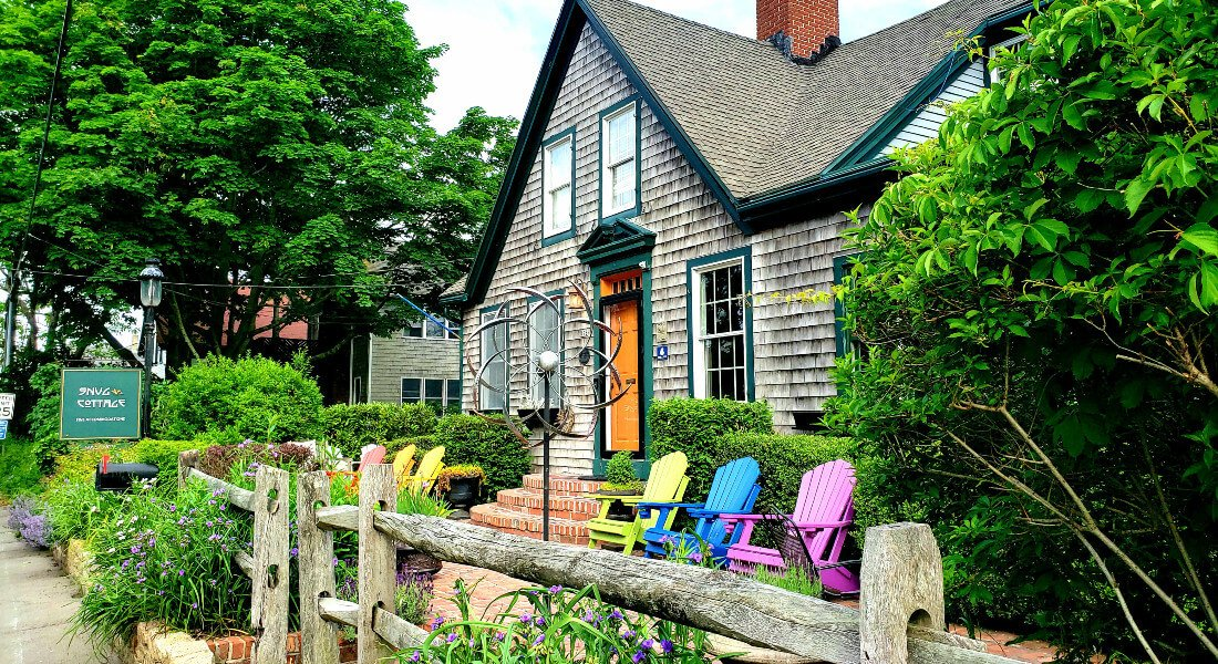 view from street facing the brown house with teal trim and red brick chimney with  Snug Cottage sign, split rail fence and bright adirondack chairs