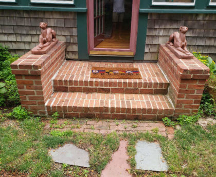 red brick steps and landing with dog statues on both sidies and welcome mat leading to full glass door entrance to home, bushes in front of brown wooded house