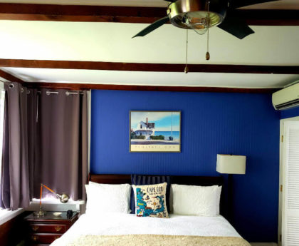 close-up view of king bed in royal blue room, nightstand, cream bed covers, cape cod pull, floor lamp, frame picture above bed