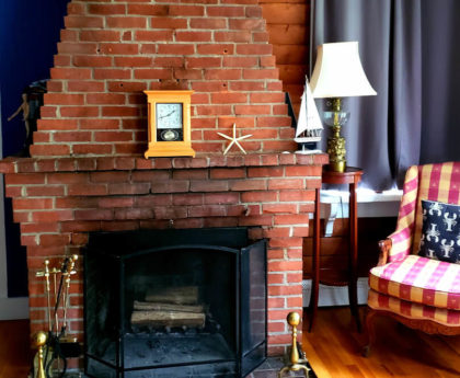 red brick fireplace from floor to ceiling with clock on mantel, red and white checkered queen anne chair, wood floor. lamp on walnut stand, blue curtains